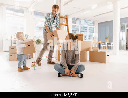 Happy family moving into new home with father and daughter carrying cardboard boxes - Stock Photo