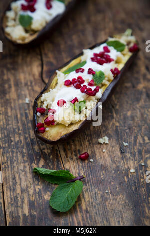 Filled aubergine, couscous, yogurt sauce, mint and pomegranate seeds - Stock Photo