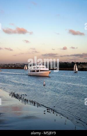Boat leaving the Marina Del Rey harbor passing  Playa Del Rey in Los Angeles, California - Stock Photo