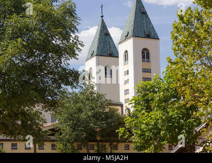 MEDJUGORJE - BOSNIA AND HERZEGOVINA - AUGUST 16 2017: Saint James belfries in Medjugorje, surrounded by nature in - Stock Photo