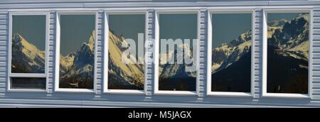 A stunning window reflection, with amazing snow covered mountains in the distance and a clear calm peaceful day - Stock Photo