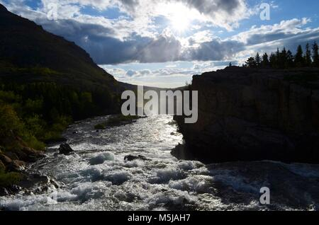 A small mountain river, flows quickly down stream, over sharp, jagged rocks, while the sun rises in the distance, - Stock Photo