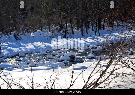 A river during the winter months, after a large snowfall, with rocks covered in snow like a mushroom cap - Stock Photo