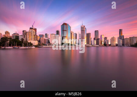 A long exposure image with the city of Brisbane reflected in the river at sunrise taken from Kangaroo Point - Stock Photo