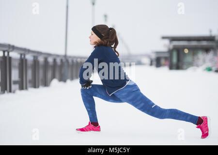 Fitness athlete female model runner doing flexibility exercise for legs before run at snow winter promenade - Stock Photo