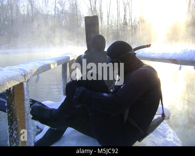 Two underwater hanters preparing for a dive on  goluboe lake - Stock Photo