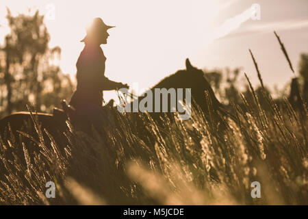 Silhouette of a woman riding a horse - sunset or sunrise - Stock Photo