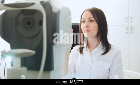 Ophthalmologist in eyes clinic doing diagnostic for patient - high technology in medicine - Stock Photo