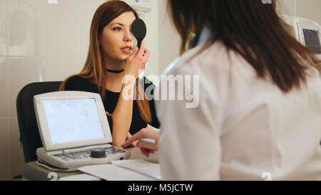 Young woman doing eye test with optometrist in medical center - Stock Photo
