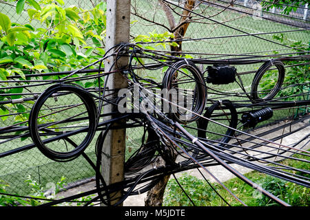 very confuse and mess electric wires on electric pole - Stock Photo