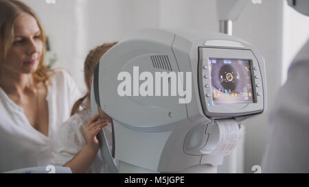 Mother and daughter in the ophthalmologist's room - optometrist in clinic checking little child's eyesight - Stock Photo