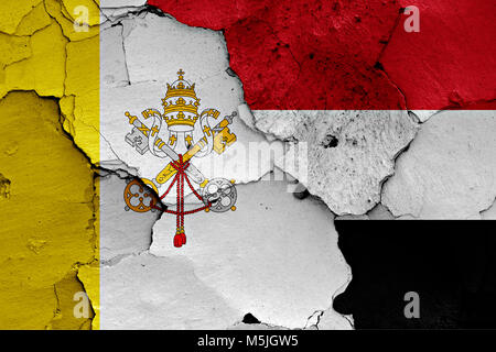 flag of Vatican and Yemen painted on cracked wall - Stock Photo