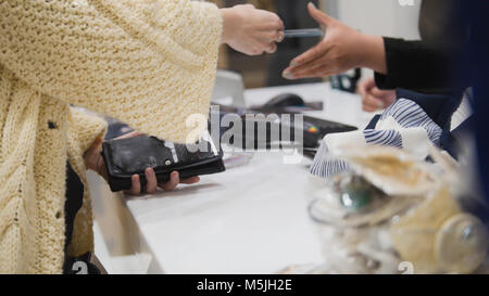 Woman paying by credit card in dress store - trading concept - Stock Photo