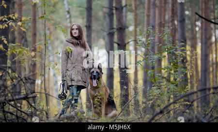 Young attractive girl and her pet - german shepherd - walking on a autumn forest - Stock Photo