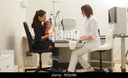 Mother and daughter in the ophthalmologist's room- optometrist in clinic checking little child's vision - Stock Photo