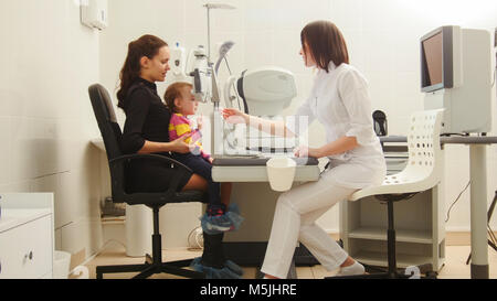 Mother and child in the ophthalmologist's room- optometrist in clinic checking little child's vision - Stock Photo