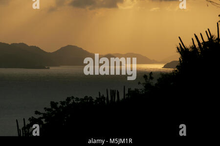 The sun sets over the island of St. Thomas as seen from the island of St. John in the U.S. Virgin Islands. - Stock Photo