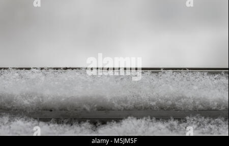 the snow falls on the windowsill. Close-up - Stock Photo