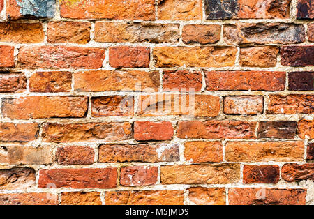 Weathered old red brick wall as background texture - Stock Photo