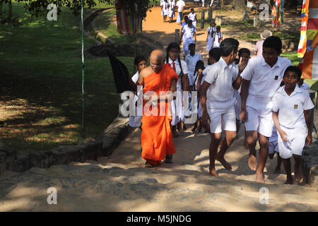 Polonnaruwa North Central Province Sri Lanka School Children And Monk Climbing Stairs to See ruins - Stock Photo