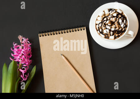 Workspace for blogger with notebook of craft paper, pencil, cup of coffee, flower on black background. Copy space. - Stock Photo