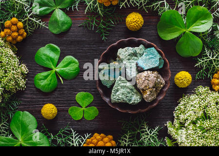 Ceramic Bowl of Green Aventurine and Pyrite with Shamrocks and Mixed Foliage on Dark Table - Stock Photo