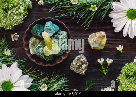 Green Aventurine, Green Calcite and Pyrite with Mixed Botanicals on Dark Table - Stock Photo