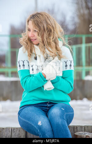 girl with curly hair in a green sweater, mittens and headphones, outdoor portrait - Stock Photo