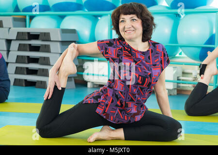 Woman doing yoga exercise in the gym - Stock Photo