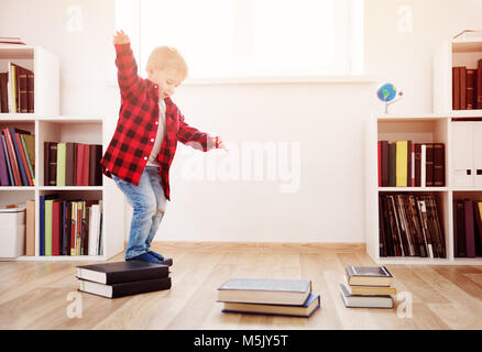 Three years old child sitting among books at home - Stock Photo