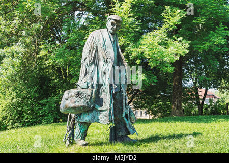 The bronze statue of a tall man with a bag, glasses and cap is located in the Tivoli Park Ljubljana, Slovenia, Europe - Stock Photo