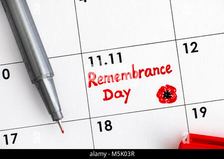 Reminder Remembrance Day in calendar with red pen. Close-up. - Stock Photo