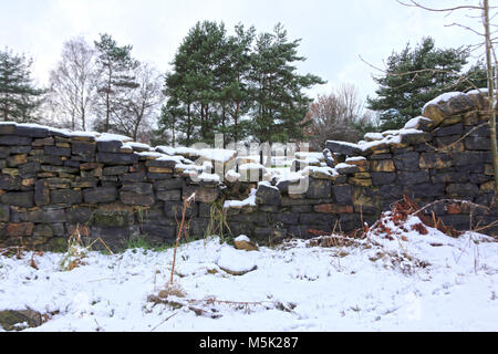 Collapsed dyke wall covered in snow in countryside - Stock Photo