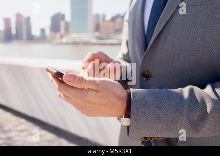 Businessman using his cell phone on a rooftop in the city - Stock Photo