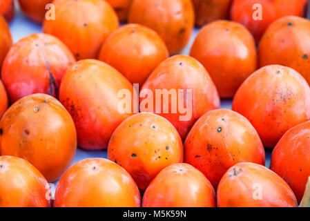Persimmon fruits for sale in market close - Stock Photo