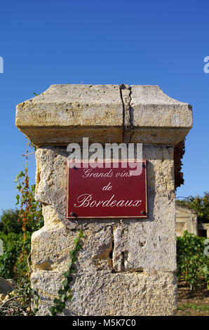 Street sign 'grands vin de bordeaux' with wine in background. Bordeaux, Gironde, France - Stock Photo