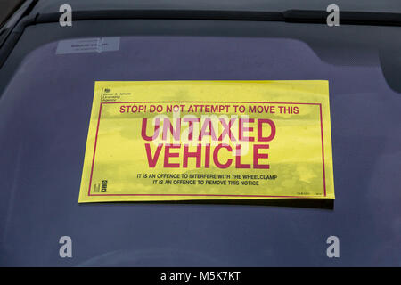 Warning sticker attached to a vehicle penalised for unpaid vehicle tax - Stock Photo