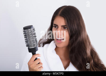 Young Woman In Bathrobe Holding Comb Looking At Hair Loss At Home - Stock Photo
