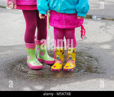 Children's feet in rubber boots in a puddle after rain. Selective focus. - Stock Photo