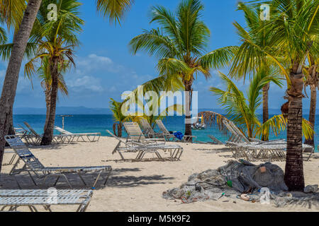 White beach with sunbeds, many palms, blue sky, a fisher net and turquoise ocean in the caribbean sea, Dominican - Stock Photo