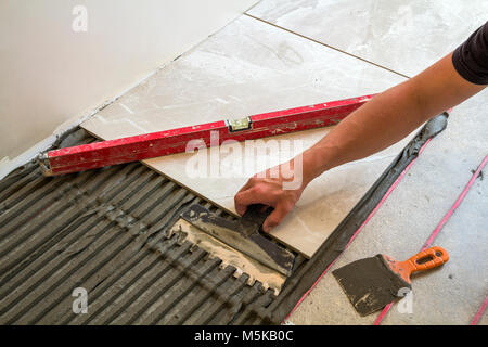 Laying Ceramic Tiles Man Placing Ceramic Floor Tile In Position