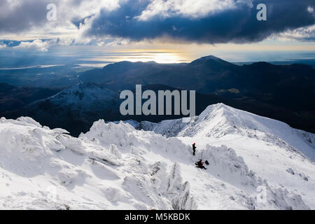 Dramatic view to west coast from Snowdon south ridge at Bwlch Main with snow in winter in Snowdonia National Park. - Stock Photo