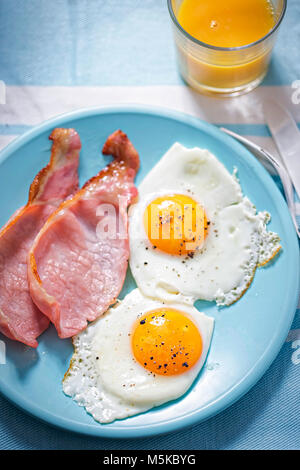 Fried eggs with bacon and orange juice - Stock Photo