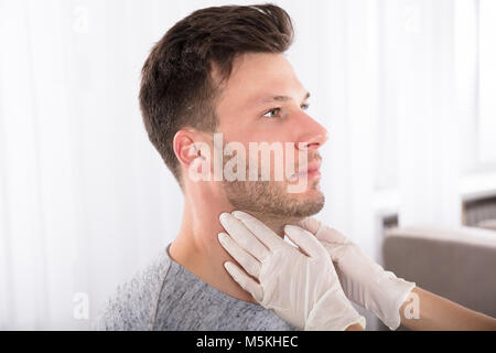 Doctor Performing Physical Exam Palpation Of The Thyroid Gland - Stock Photo
