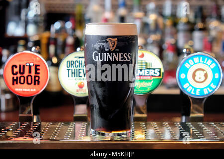 Pint of Guinness in front of different ale and beer pumps, The Merchant's Arch Bar & Restaurant, Temple Bar, Dublin, - Stock Photo