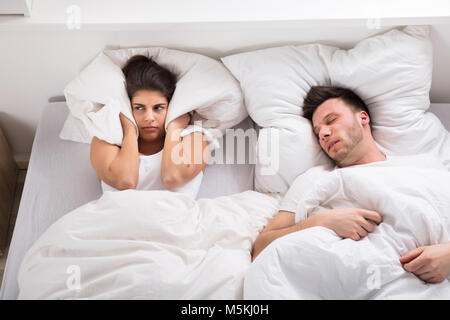 Annoyed Wife Blocking Her Ears With Pillow From Noise Of Husband Snoring - Stock Photo
