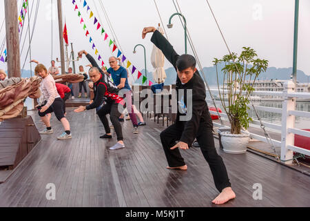 A Vietnamese man leads a group of tourists in a Tai Chi class at sunrise on the upper deck of a cruise ship in Halong - Stock Photo