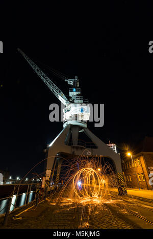 Magdeburg, Germany - February 24,2019: Night view of an old loading crane with fireball in the science harbour of - Stock Photo