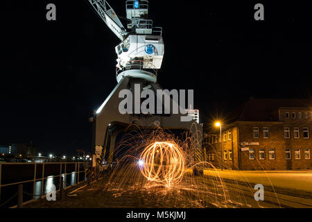 Old loading crane with fireball. Steel wool. At an old dock. - Stock Photo