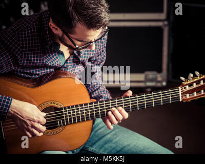 Photo of a man playing his acoustic guitar in a rehearsal studio. Focus on man's head. - Stock Photo